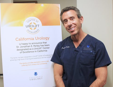 Male (Dr. Jonathan Perley) standing next to sign stating he received UroLift® Center of Excellence Recognition.