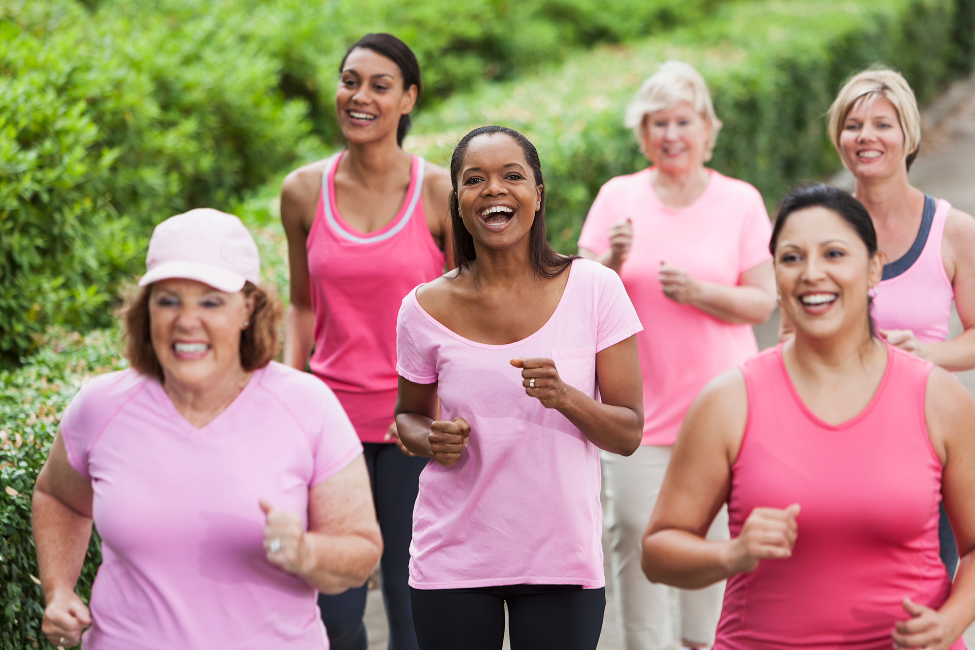 Multi-ethnic group of women wearing pink, participating in breast cancer rally.  Focus on African American woman in middle.